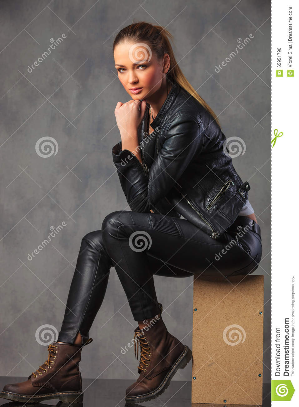 Fashionable girl in leather posing in studio background