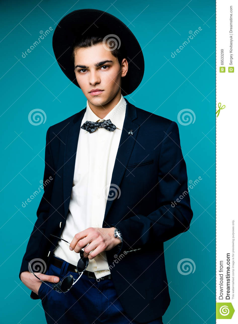 Fashionable Handsome Man in hat wearing elegant suit.