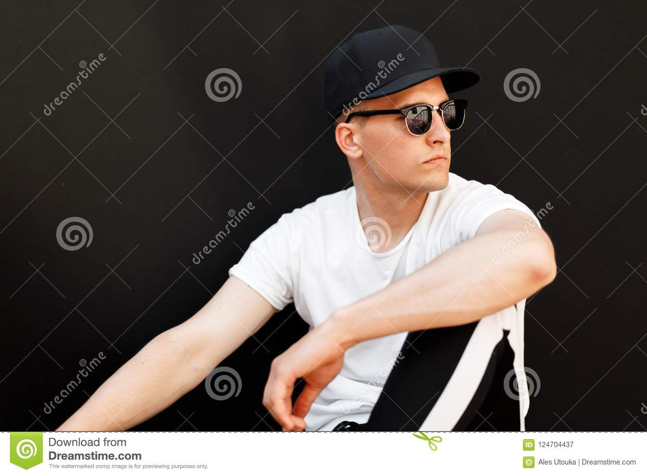 a94d8eb94011 Fashionable handsome man with sunglasses and a stylish black cap in a white  T-shirt sits on a black background