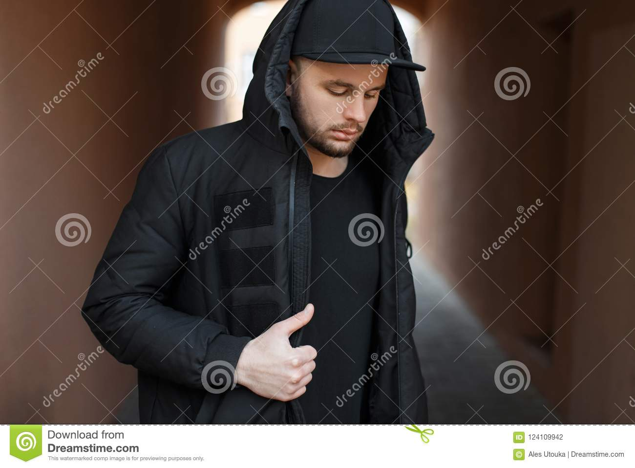 8a2c7735997 Fashionable handsome young man with a black baseball cap in a hood with a winter  jacket on the street