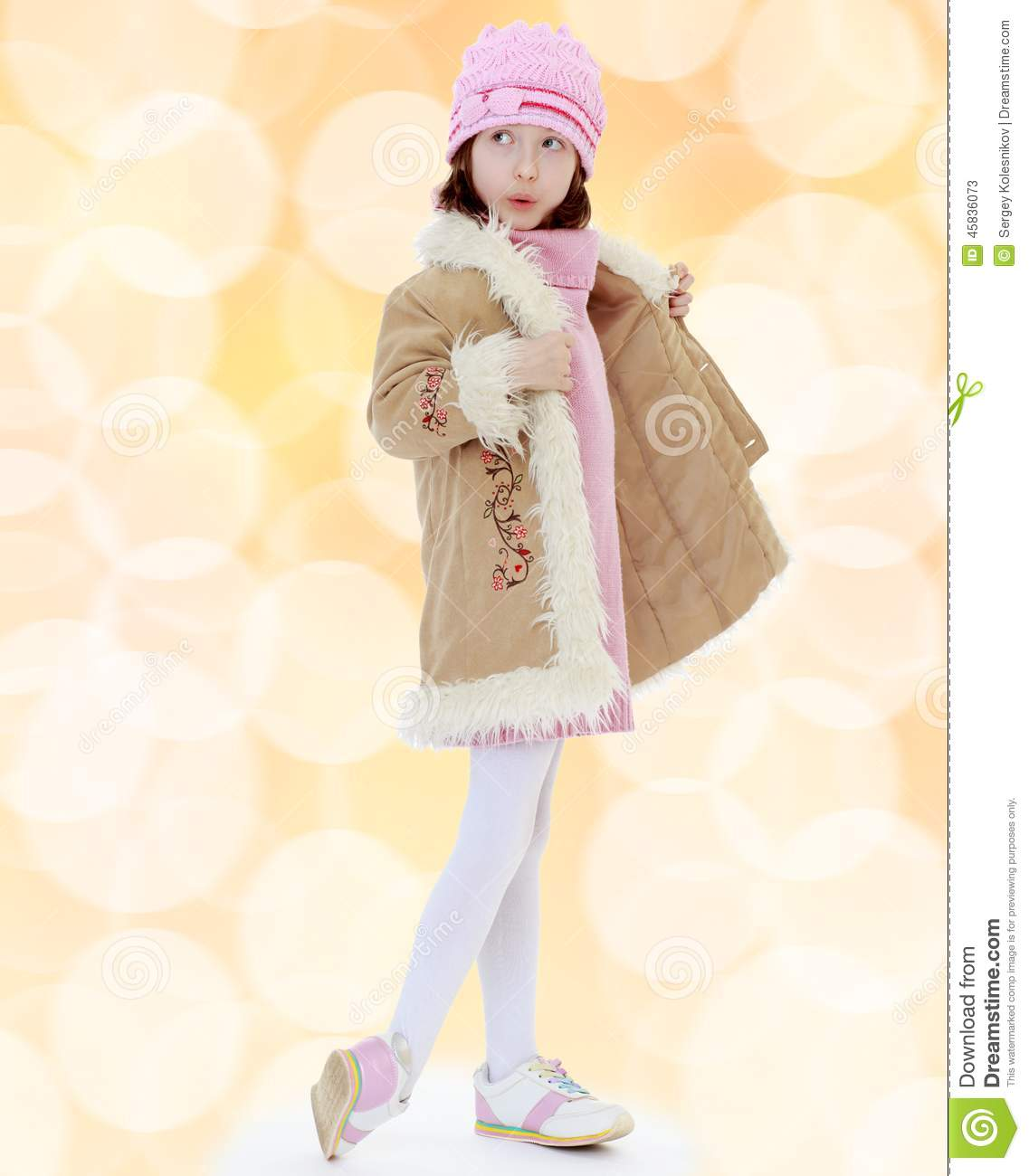 Fashionable little girl in a fur coat.