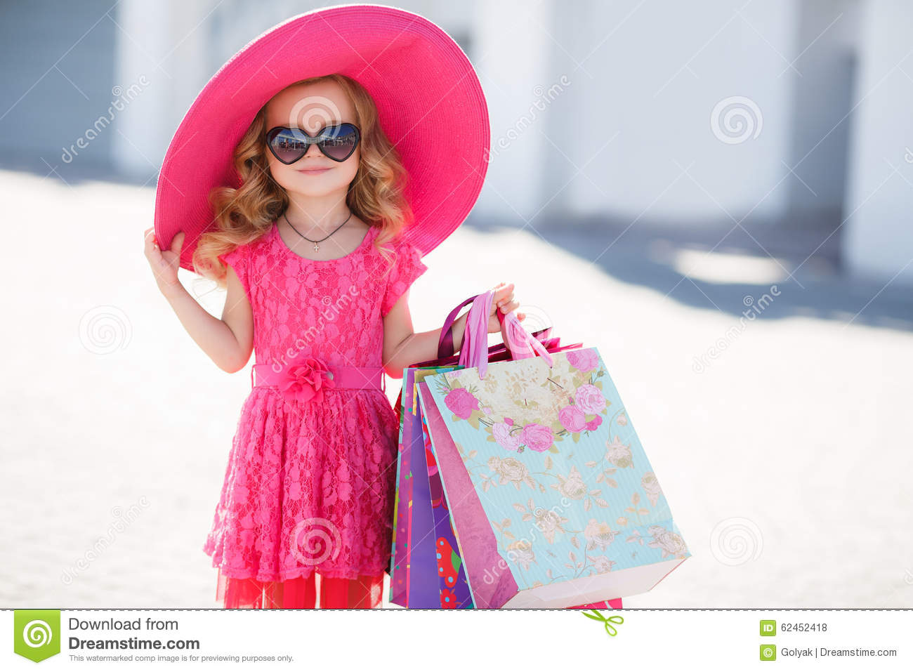 fashionable little girl in a hat with shopping bags stock