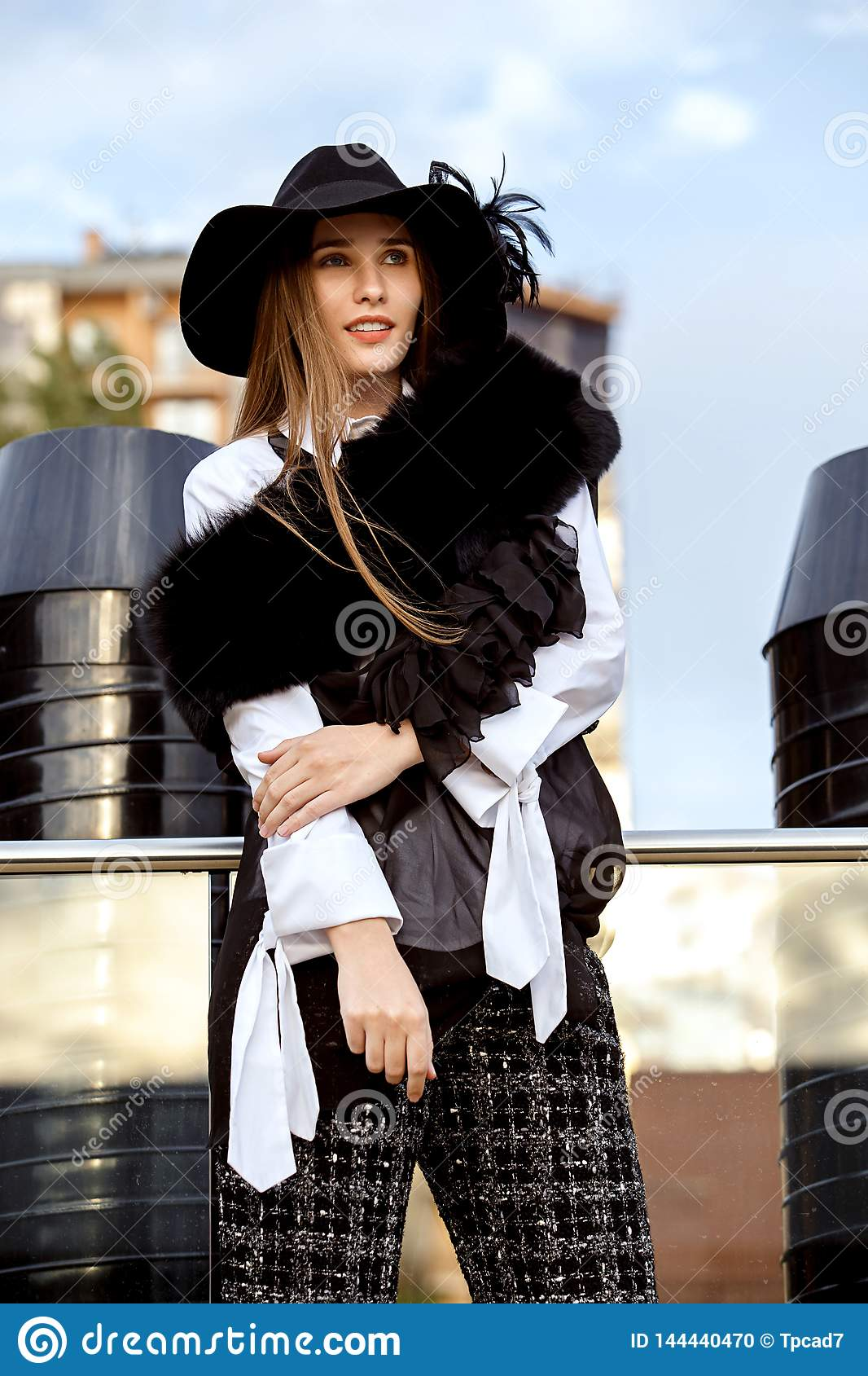 Fashionable slim long-haired girl dressed in a black stylish jacket on a white shirt, black pants and a hat with a wide