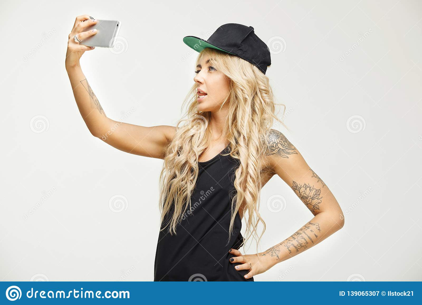 Fashionable swag girl screams face in front smartphone camera, makes a  selfie an white isolated