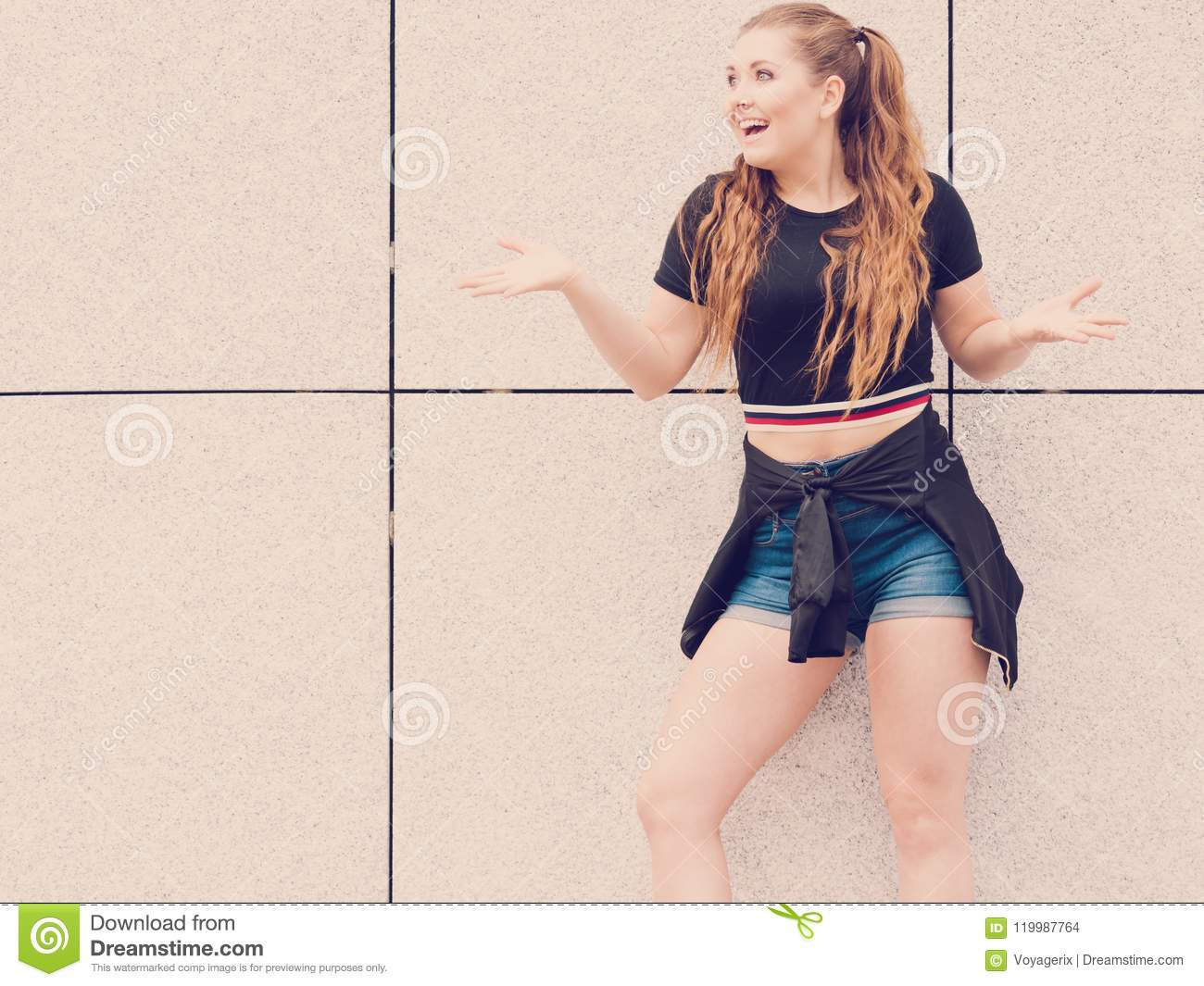 5b4757b620 Young teenage woman wearing denim shorts and black crop top. Female  presenting fashionable summer outfit.