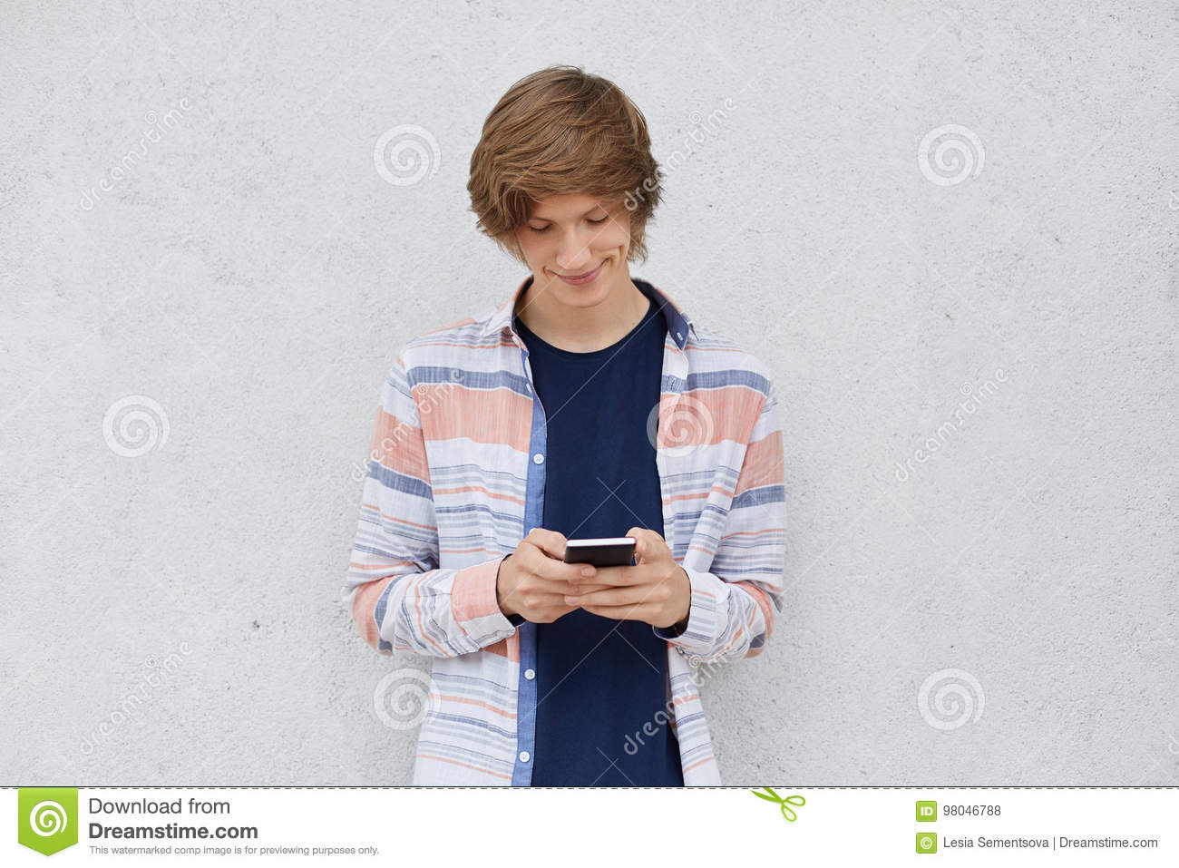 Fashionable teenage boy wearing shirt, holding cell phone in hands, messaging with friends or playing games online using free inte