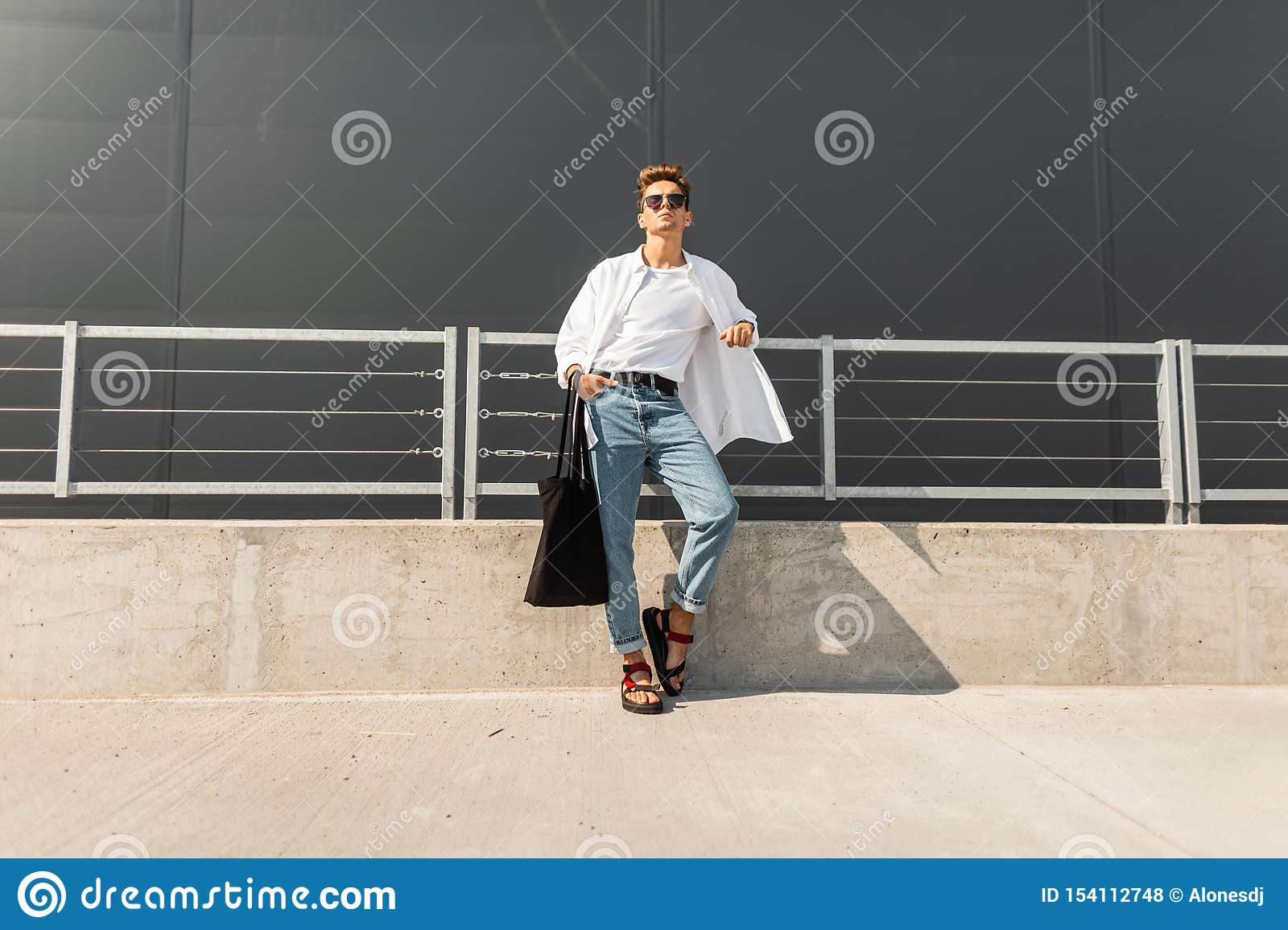 Fashionable urban young man in red sandals in a white shirt in blue jeans in sunglasses with a black bag relaxes in the street