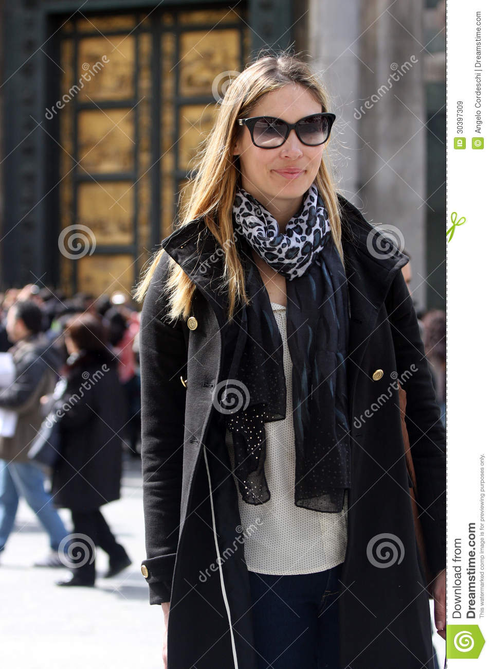 Fashionable woman with coat, bag, scarf and sunglasses