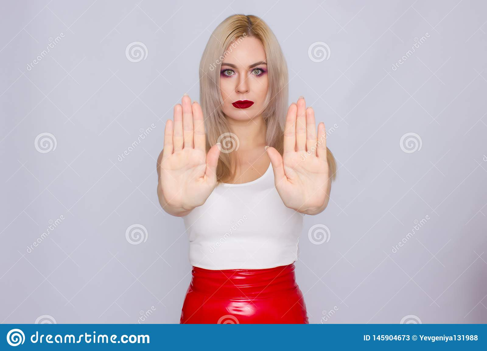 Blonde woman in red leather skirt and white shirt