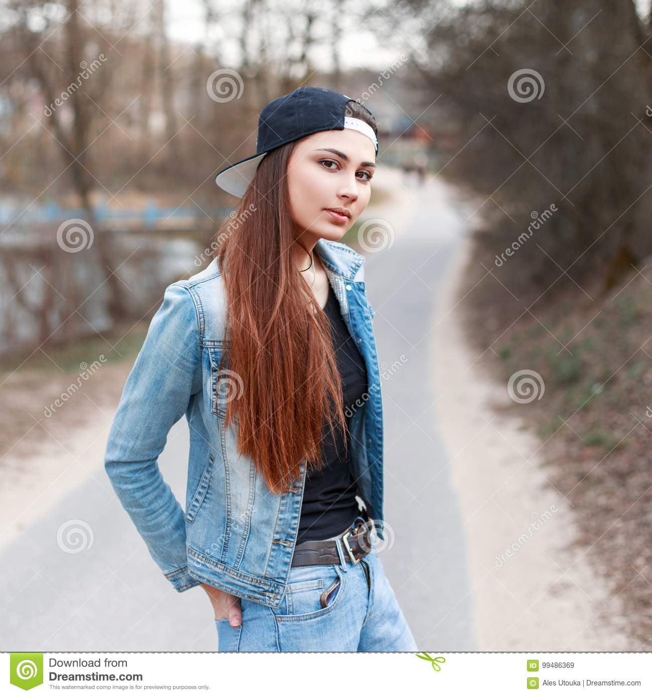 Fashionable young girl in a black cap and jeans jacket standing