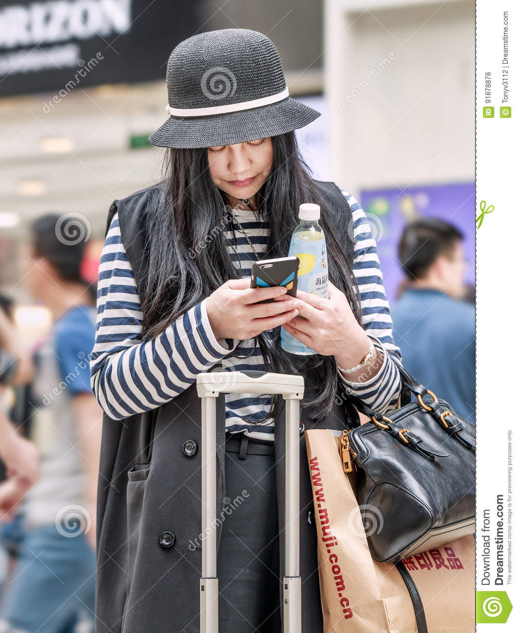 Fashionable young girl busy with her smart phone, Beijing, China