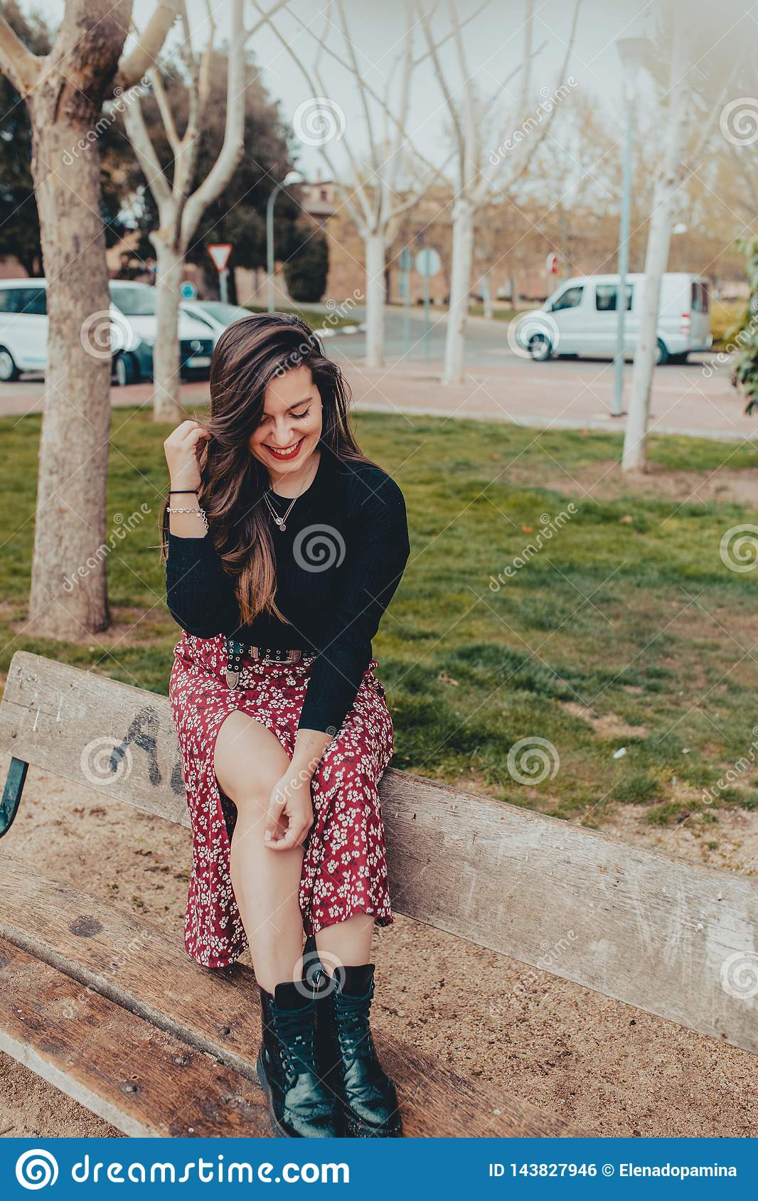 Fashionable young girl sitting on a bench laughing shyly