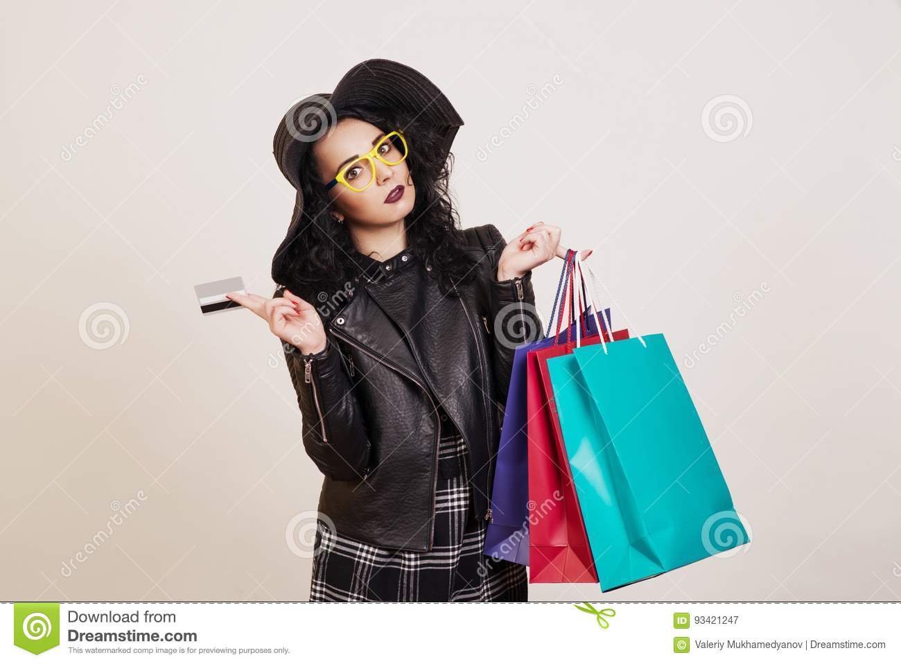 Fashionable young woman in black hat with credit card and colored shopping bags over white studio background.