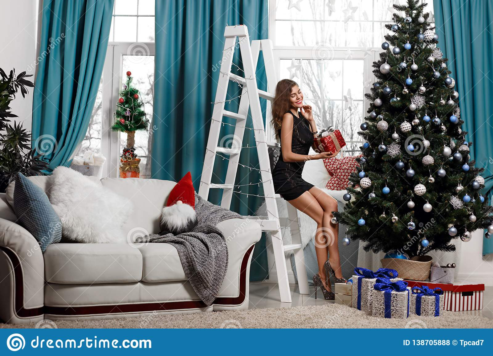Fashionable young woman in festive dress lays out gifts under the Christmas tree in the living room, enjoying Christmas.