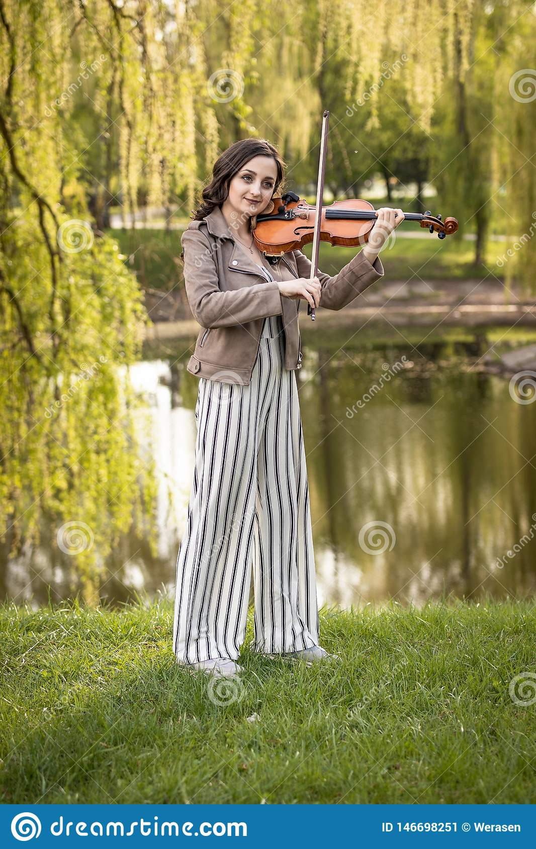 Fashionable young woman playing the violin in the park. The general plan