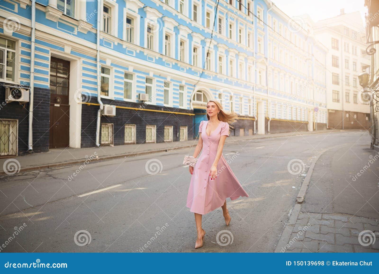 Fashionably påkläddkvinna på gatorna av en liten stad som shoppar begrepp