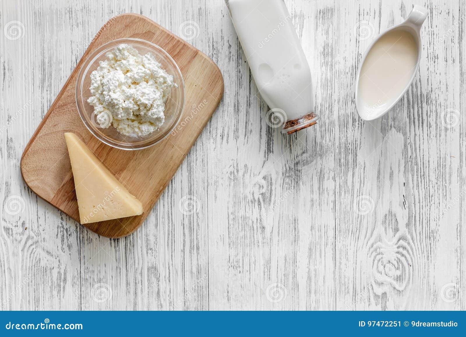 Fasoli marchewek kalafiorów karmowi naturalni smyczkowi warzywa Mleko, chałupa, ser na lekkim drewnianym tło odgórnego widoku cop