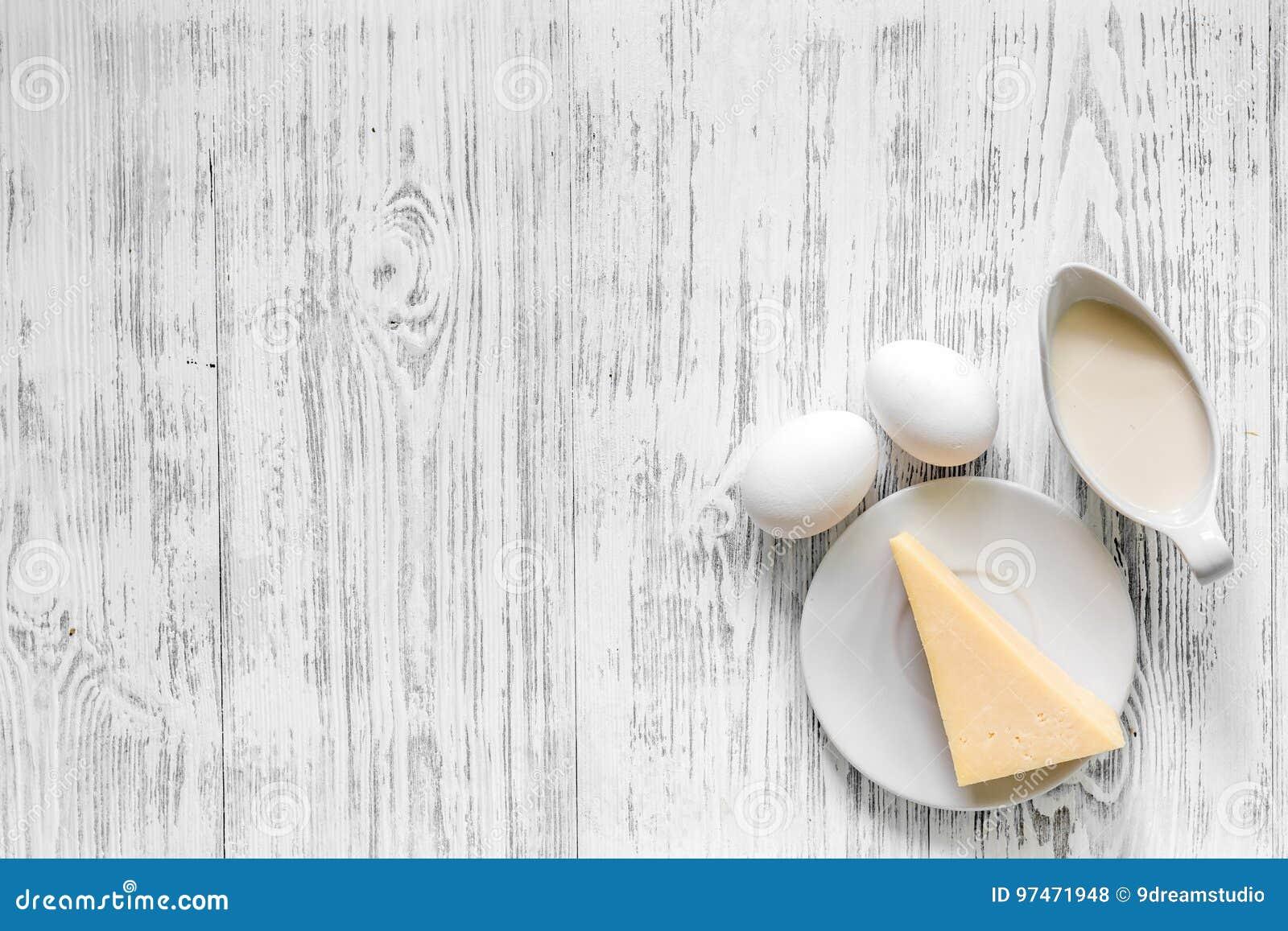 Fasoli marchewek kalafiorów karmowi naturalni smyczkowi warzywa Mleko, jajka, ser na lekkim drewnianym tło odgórnego widoku copys