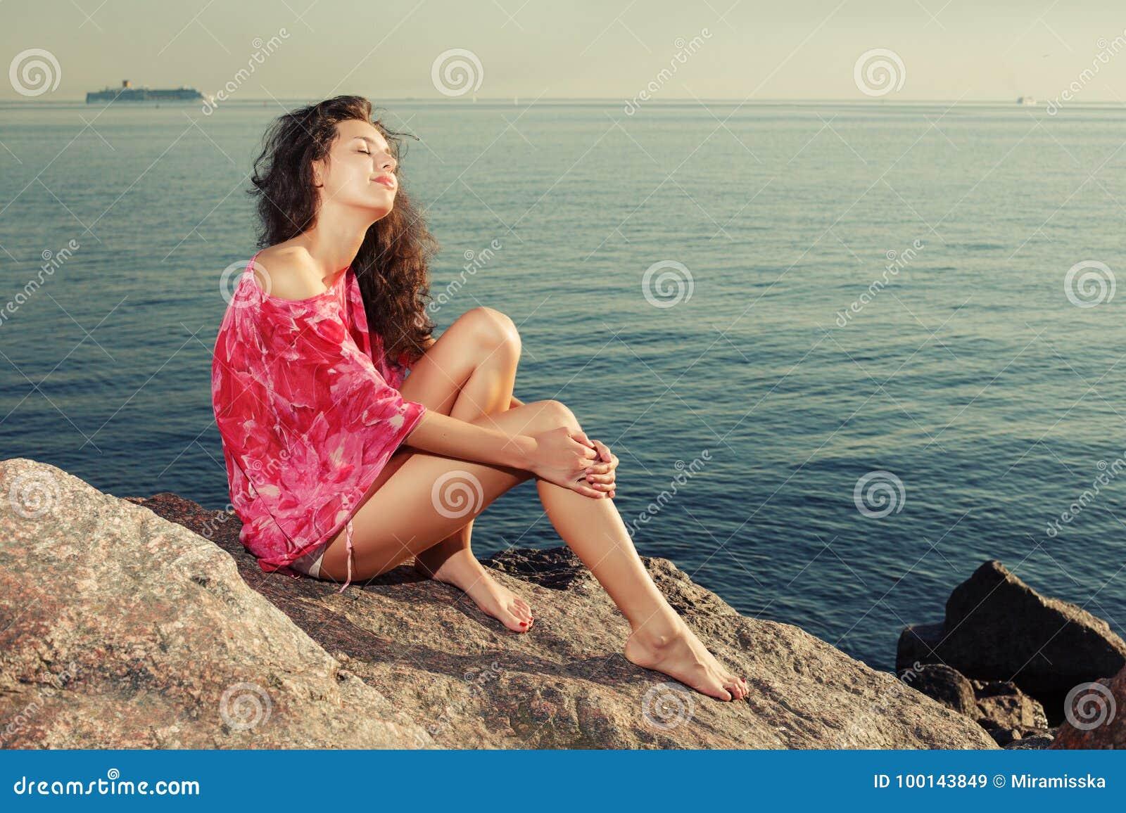 Fasonuje dziewczyny na plaży na skałach przeciw tłu