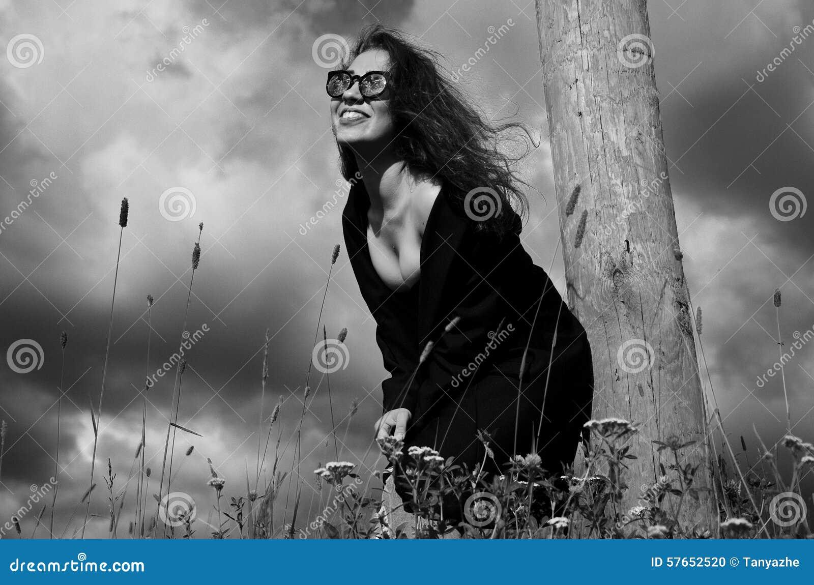 Fasonuje dziewczyny w czarnej żakiet pozyci w trawie blisko drewnianego słupa