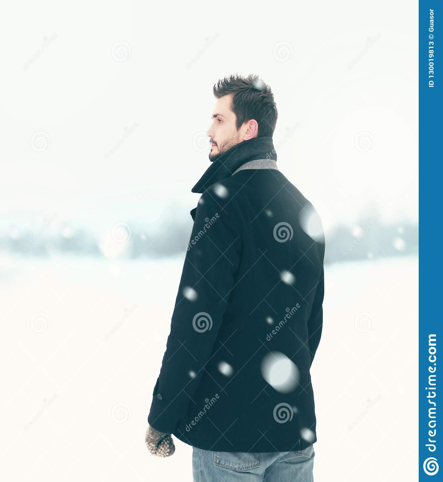 Fasonuje eleganckiego bezpłatnego mężczyzny w zima śnieżycy spojrzeniach daleko od