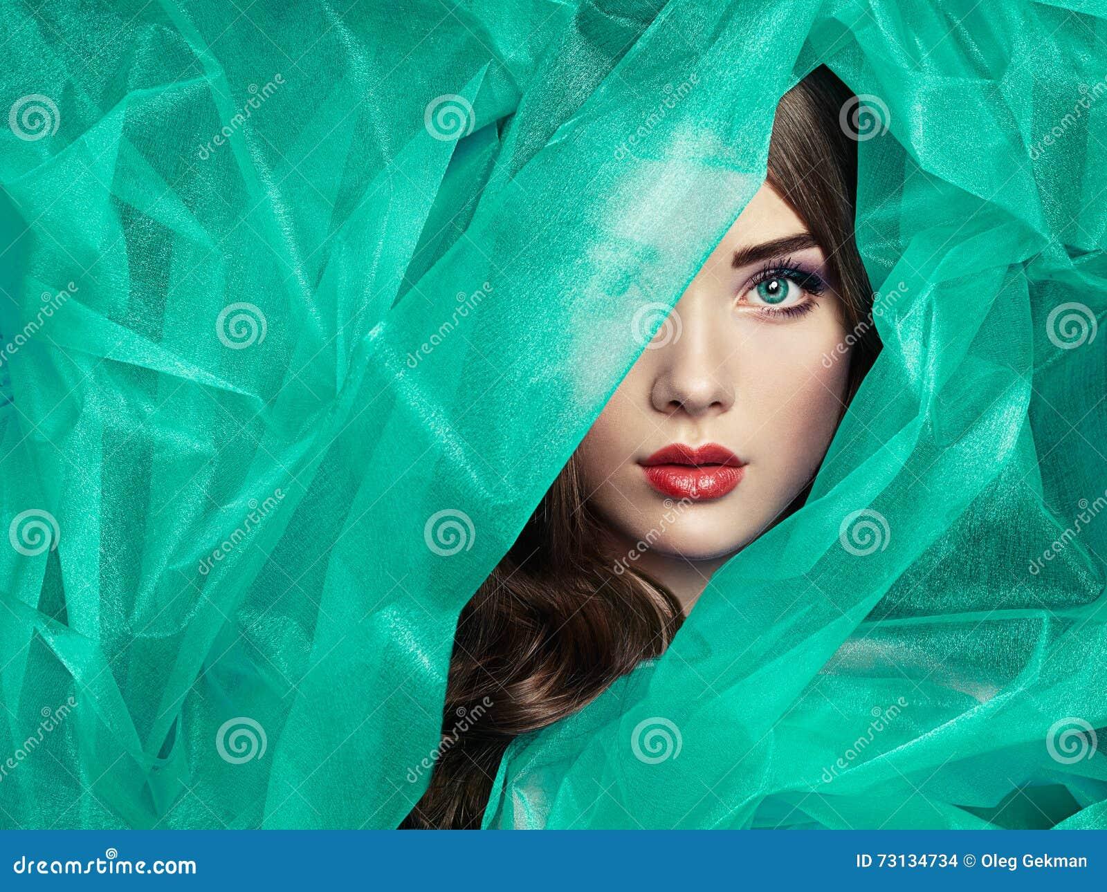 Fasonuje fotografię piękne kobiety pod turkusową przesłoną
