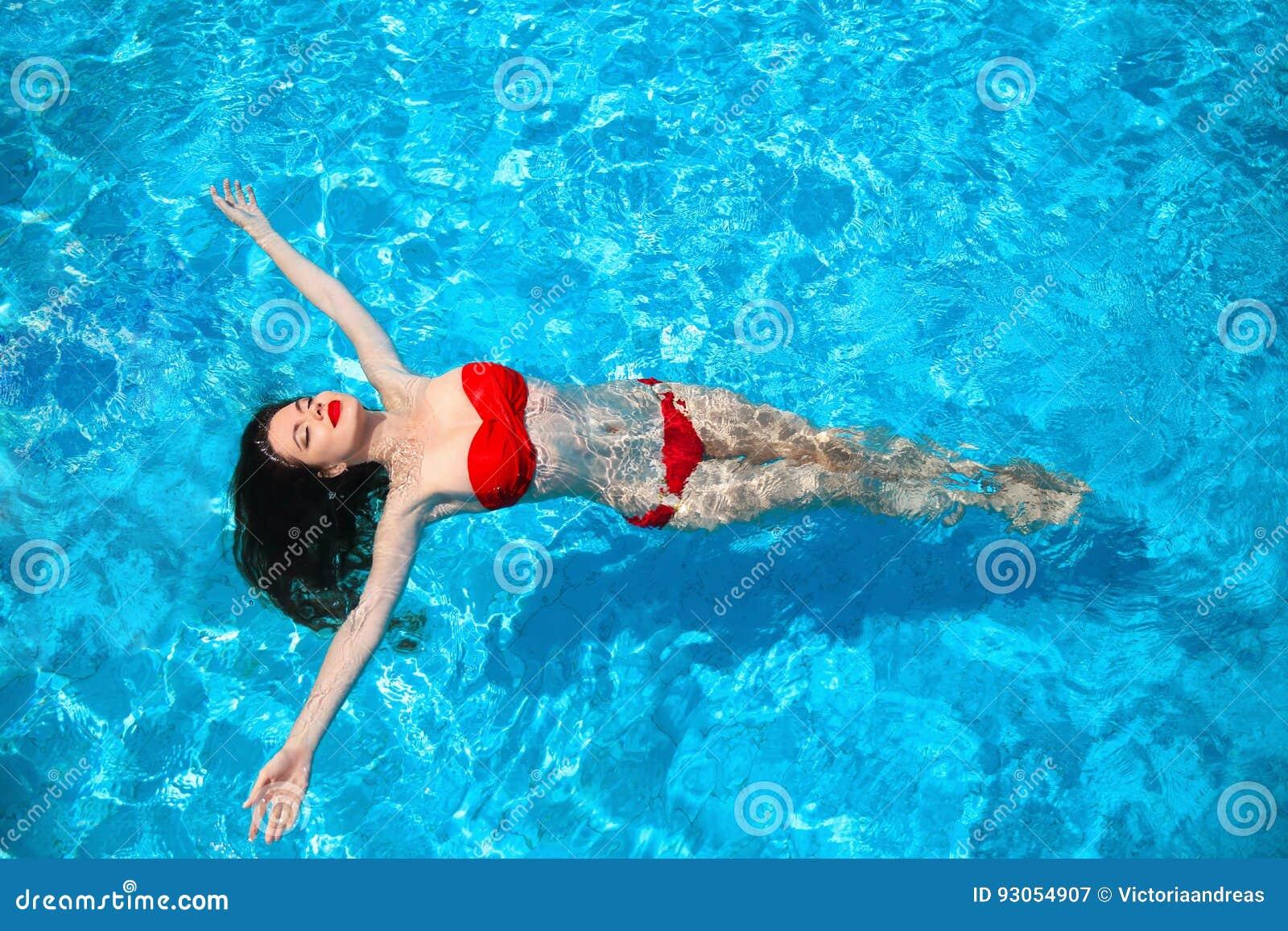 Fasonuje idylliczny seksowny bikini garbnikującego kobiety dopłynięcie na powierzchni