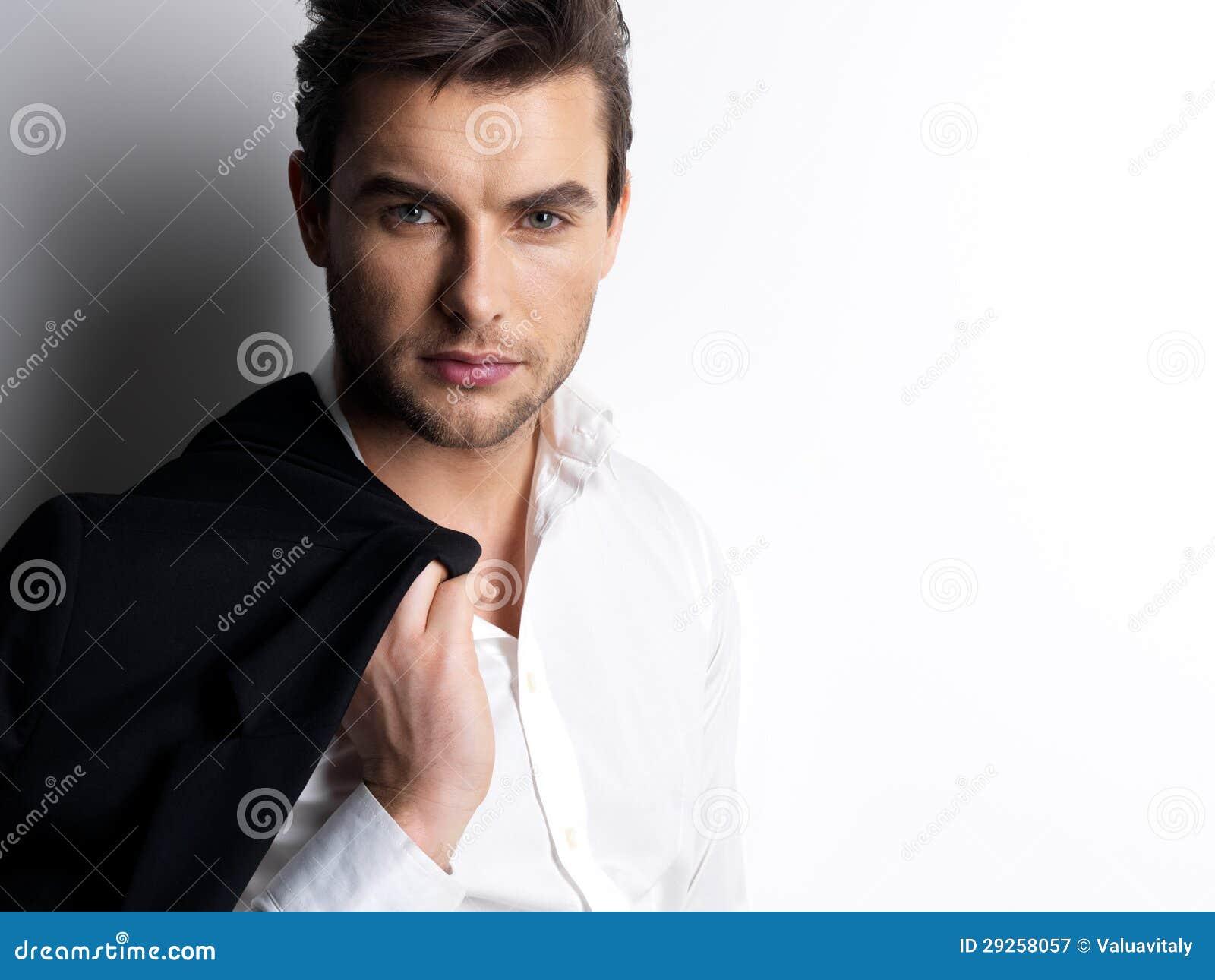 Fasonuje młodego człowieka w białych koszula chwytach czarna kurtka