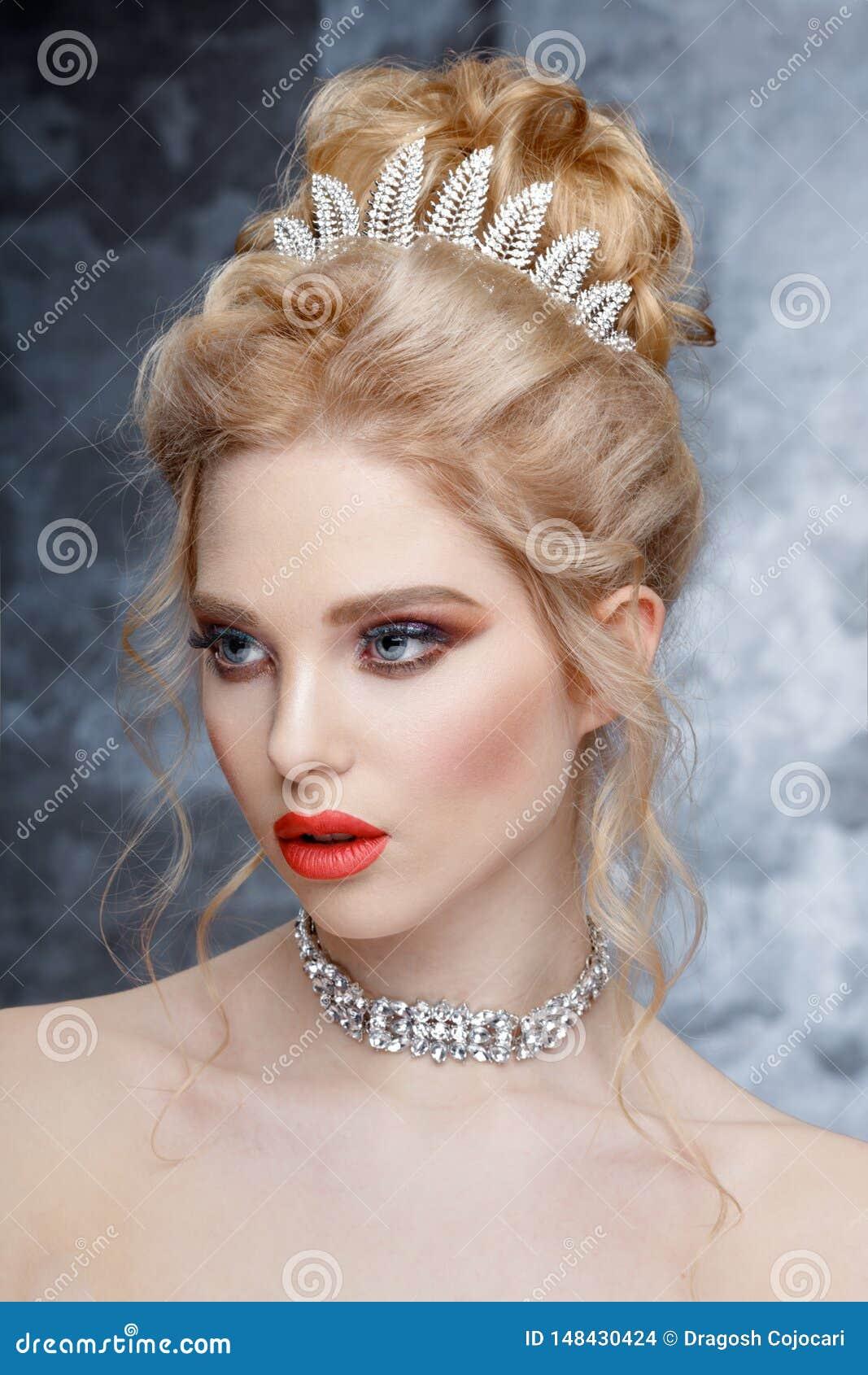 Fasonuje portret pi?kna kobieta z tiar? na g?owie elegancka fryzura Perfect makija? i bi?uteria Koralowe wargi