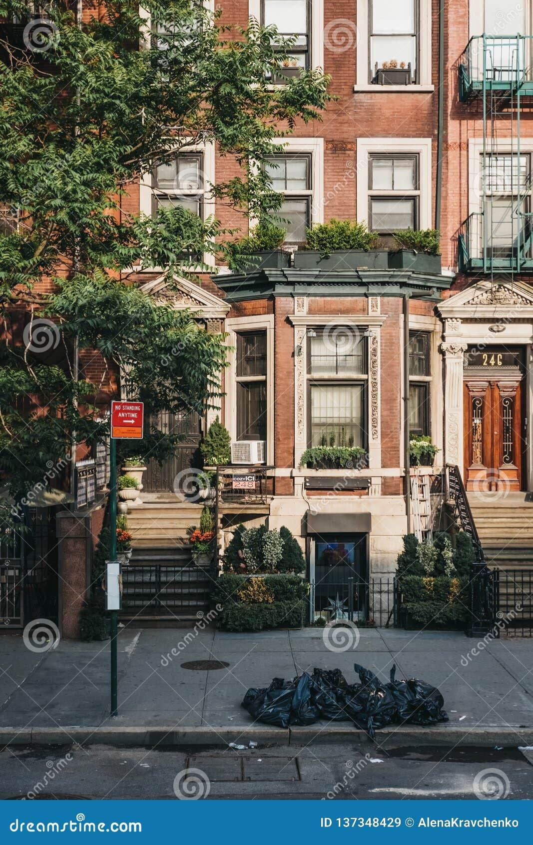 Fassade eines typischen New- Yorkhauses mit einem krummen Rücken, Abfall in den schwarzen Behältern vor ihm
