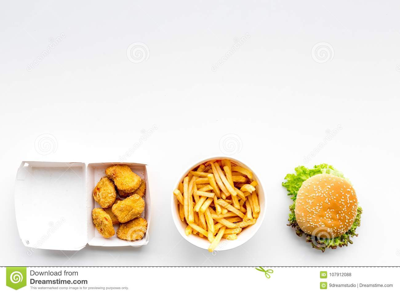 Fast food. Chiken nuggets, burgers and french fries on white background top view space for text