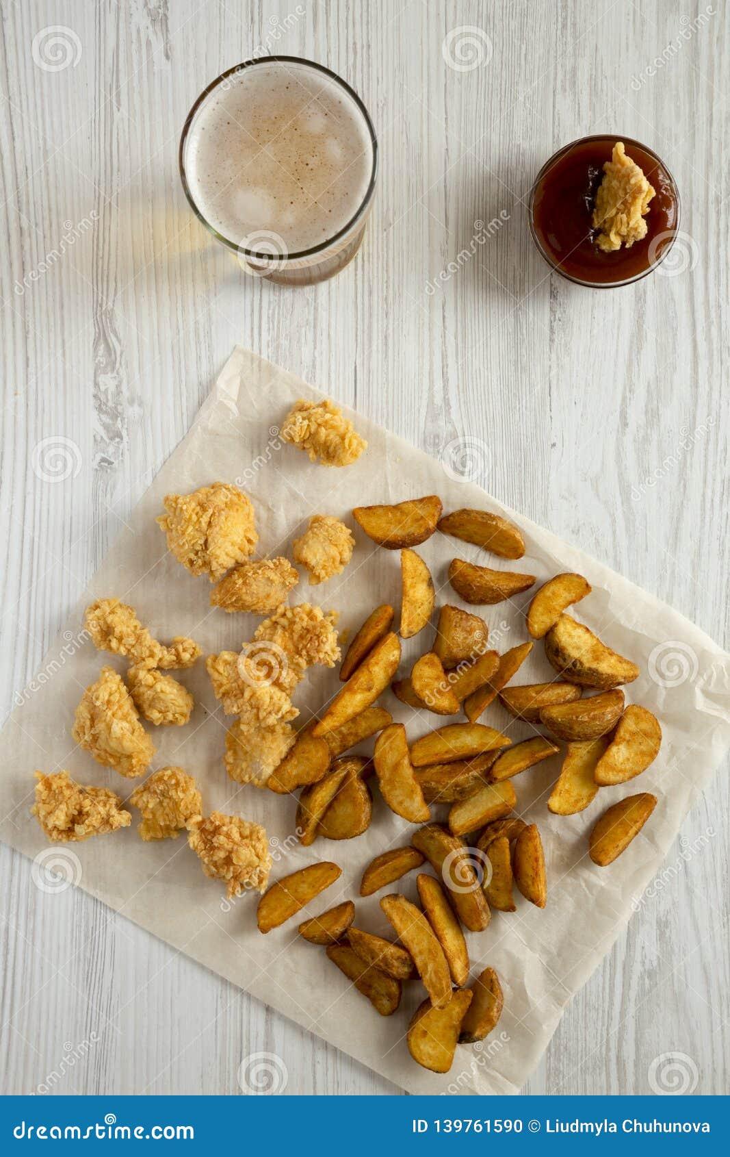 Fast food: cunhas da batata, mordidas da galinha, cerveja e molho fritados em uma tabela de madeira branca, vista superior do BBQ