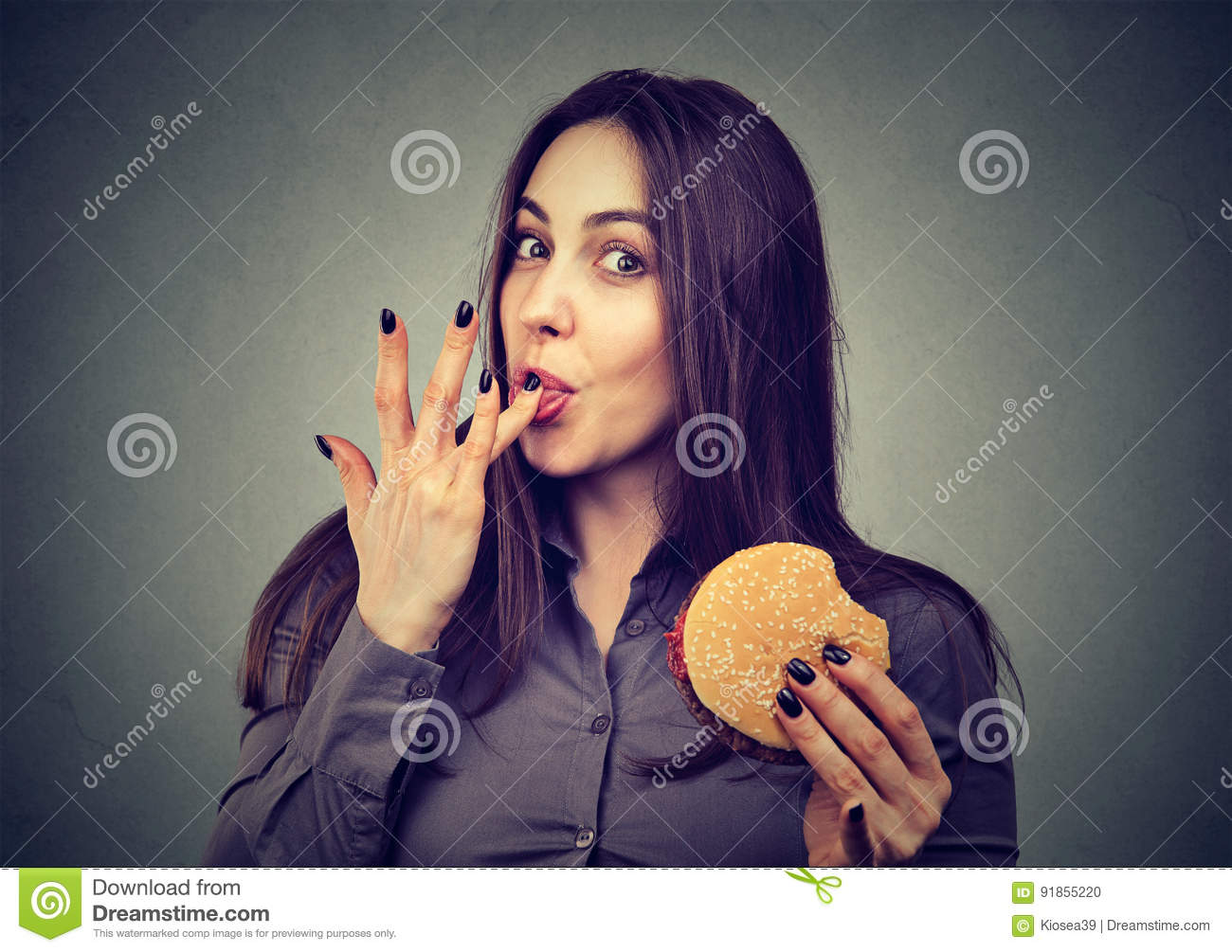 Fast food is my favorite. Woman eating a hamburger enjoying the taste