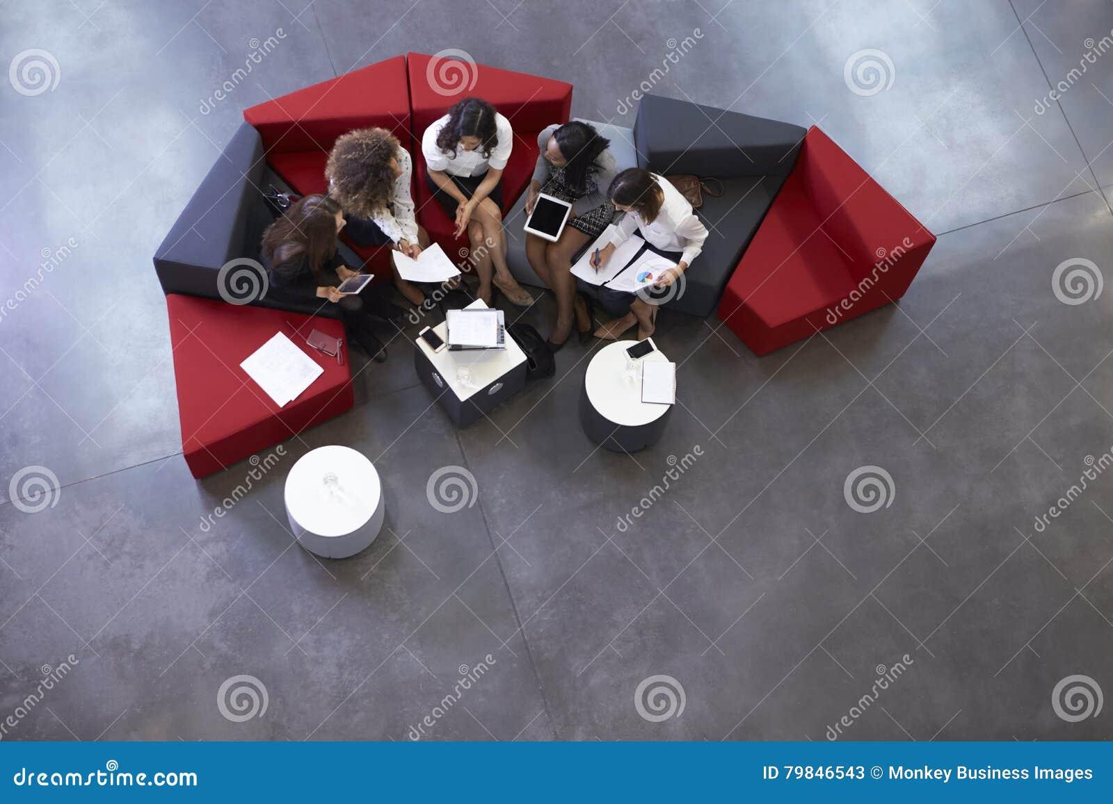Fast utgiftskott av affärskvinnor som möter i lobby av kontoret