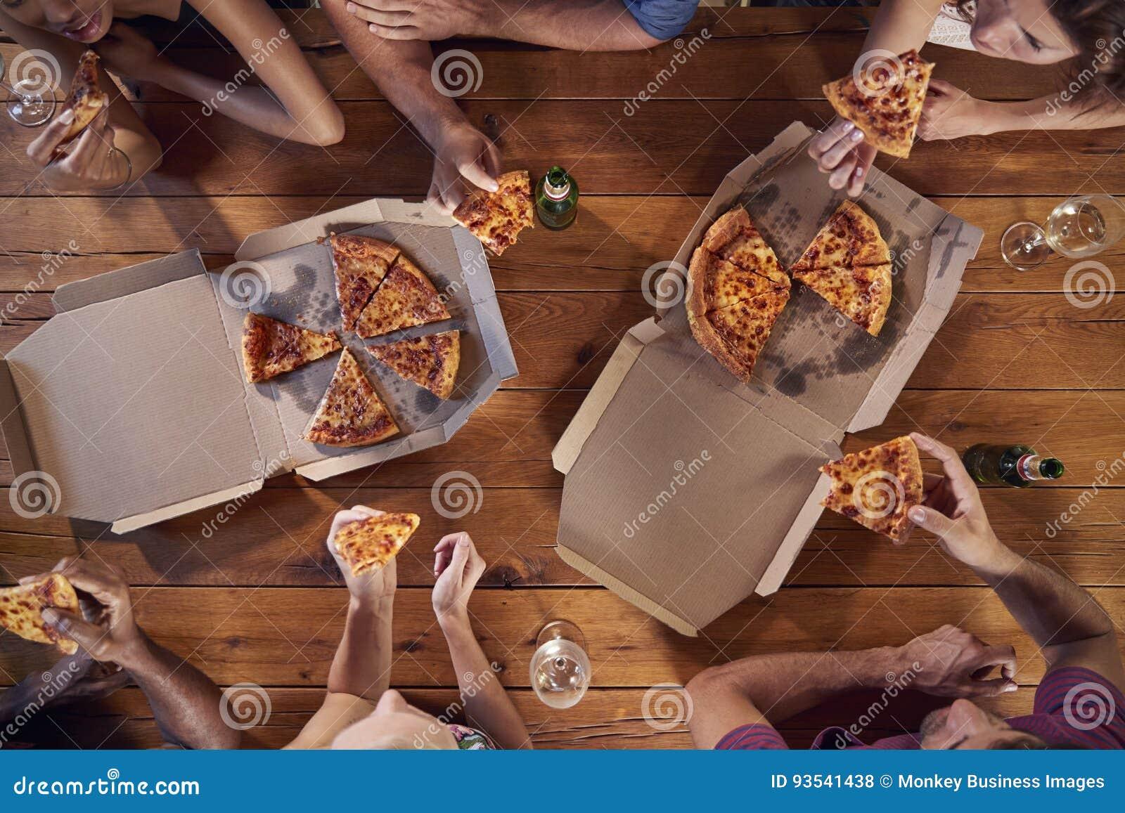 Fast utgiftskott av vänner på en tabell som delar tagande-bortpizza