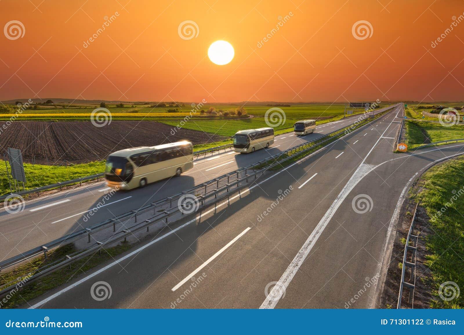 Fasten Reisebusse in Folge auf der Autobahn bei Sonnenuntergang