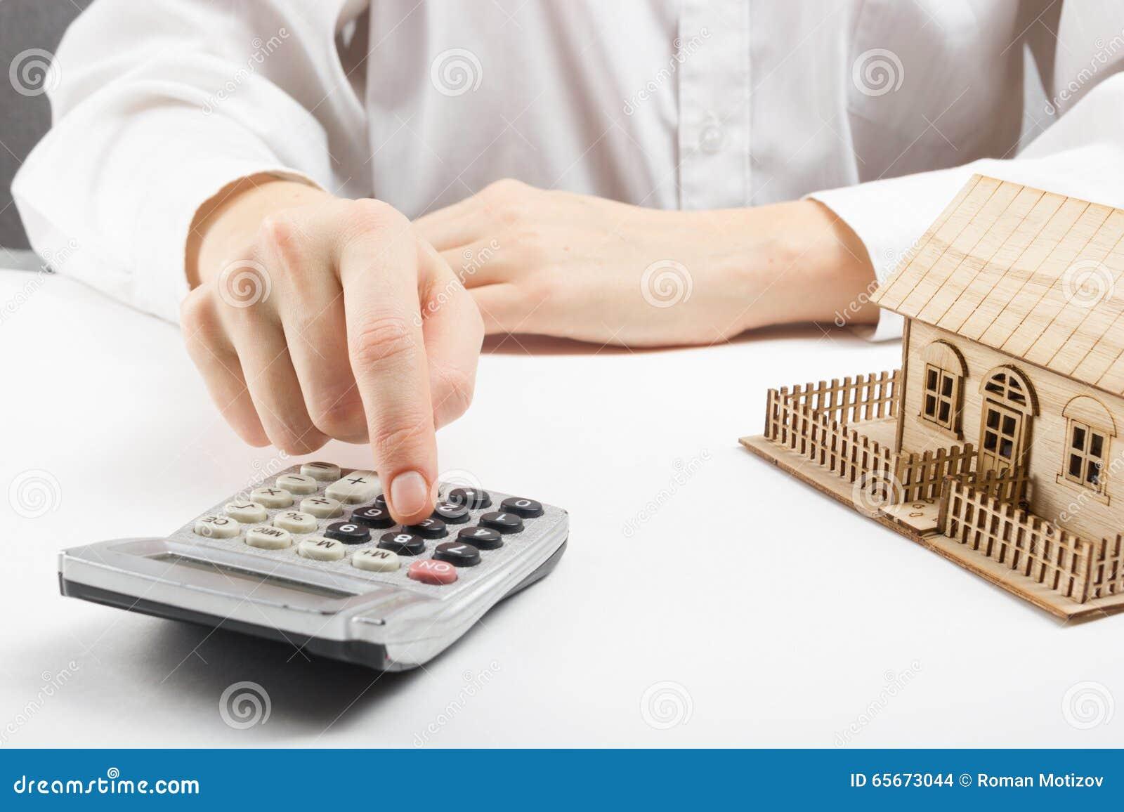 Fastighetbegrepp - affärsman som räknar bak hem- arkitektonisk modell