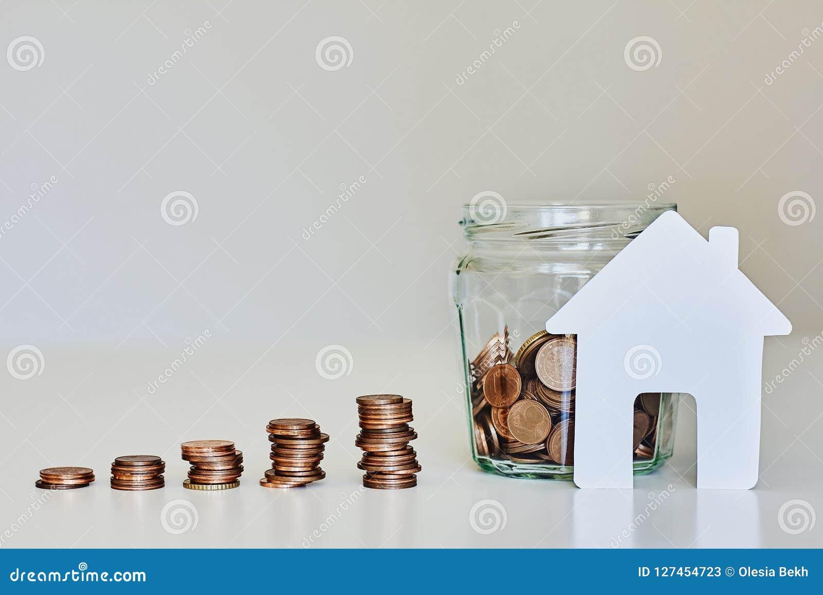 Fastigheten intecknar begrepp Glass krus mycket av mynt, buntar av mynt och vitbokhuset