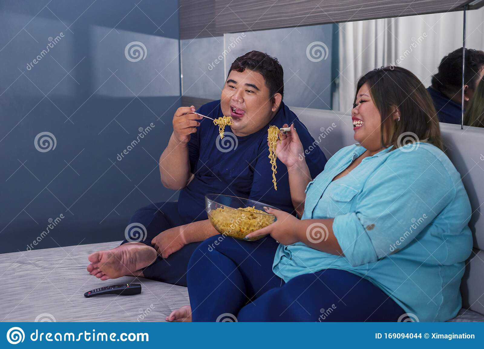 fat couple eating noodle happily while watching tv stock