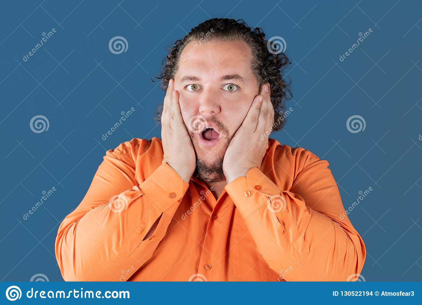 Fat man in orange shirt holds his hands over his face. He is very surprised