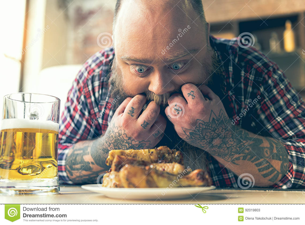 Fat man staring at meat with appetite