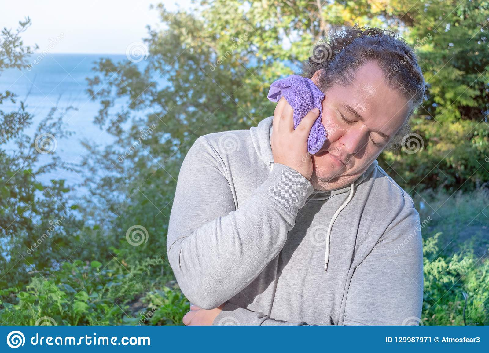Fat man wipes his face with a towel standing on the ocean. Sport and a healthy lifestyle