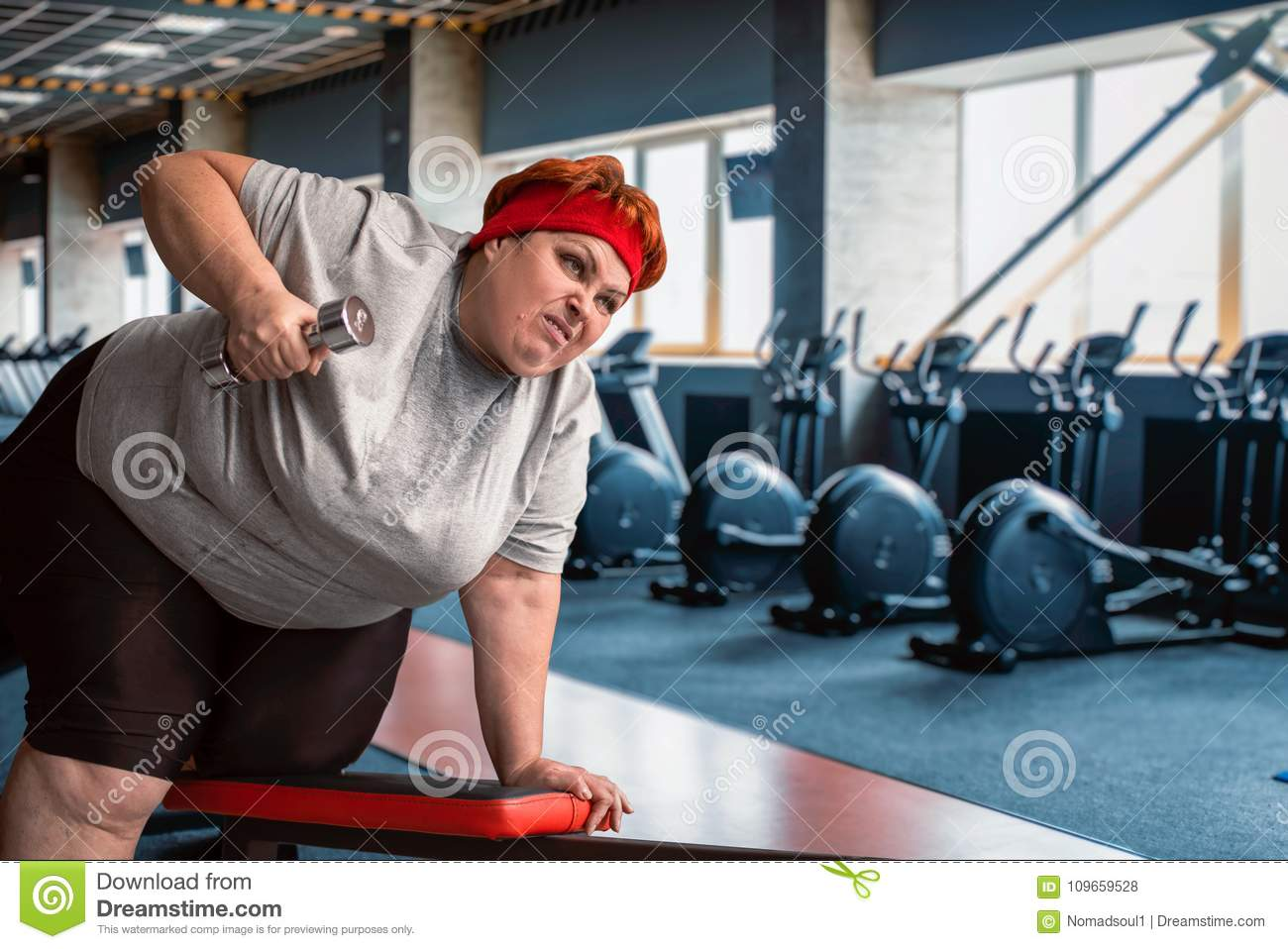 Fat sweaty woman using dumbbells in gym stock photo image of