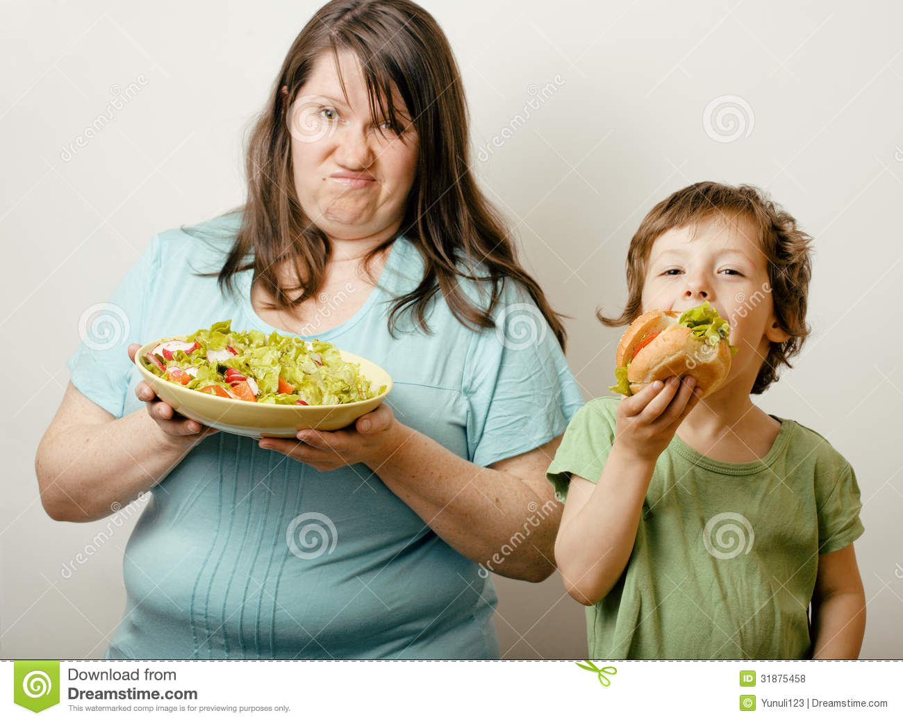 fat woman holding salad and little cute boy with hamburger stock