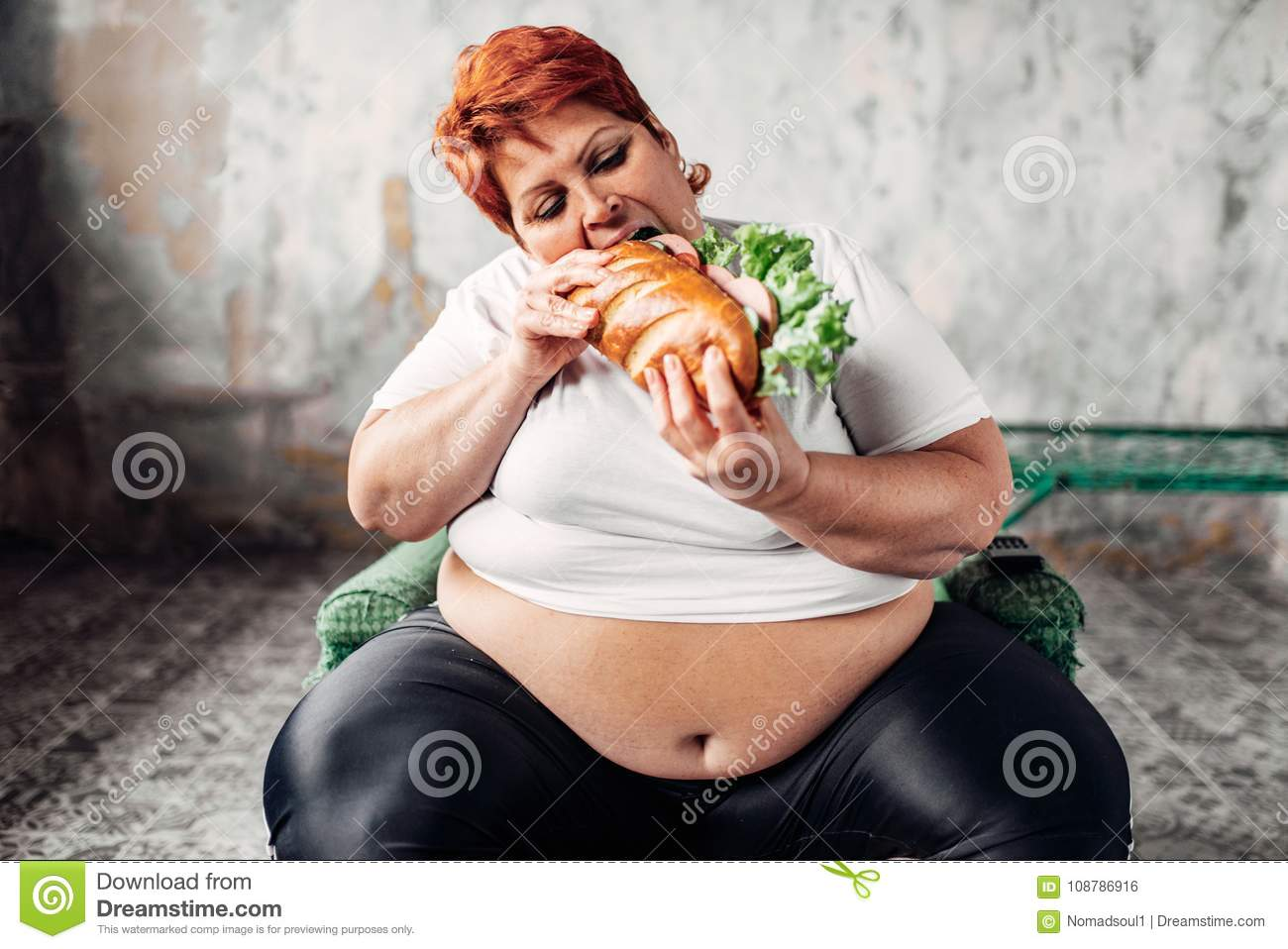 Fat Woman Sits In Chair And Eats Sandwich, Bulimic Stock