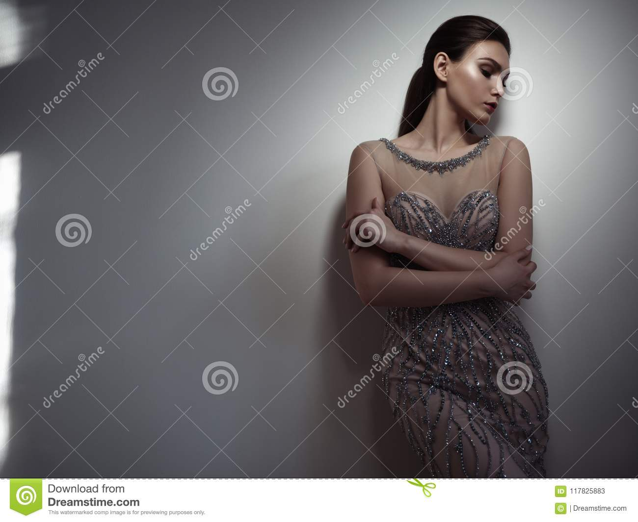 Fatale brunette with expressive dark make up and sleeked hair is posing in the studio on the gray background in the smart beige ev
