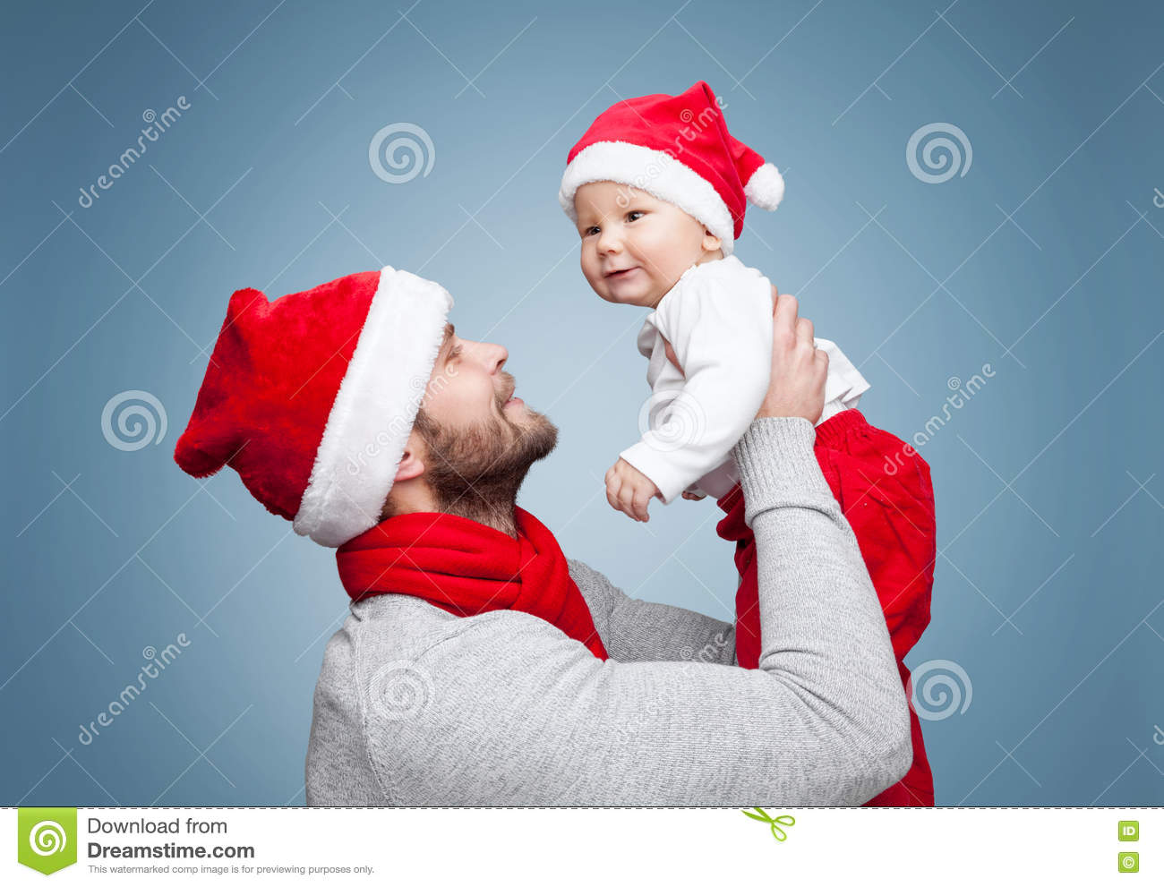 Father With Baby Boy Wearing Santa Hats Celebrating Christmas Stock ...