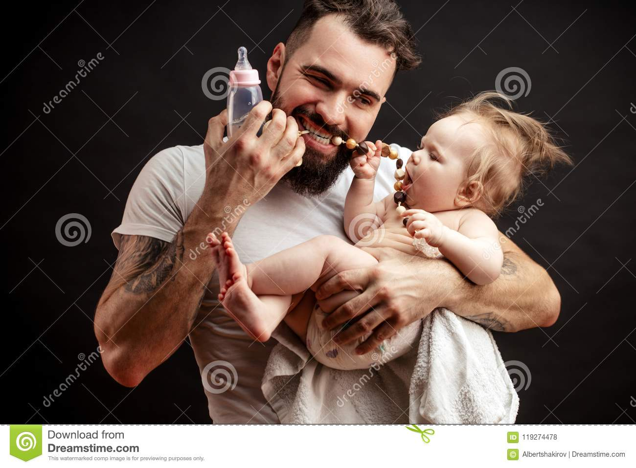 Father And Baby Daughter Playing With Chaplets Stock Photo