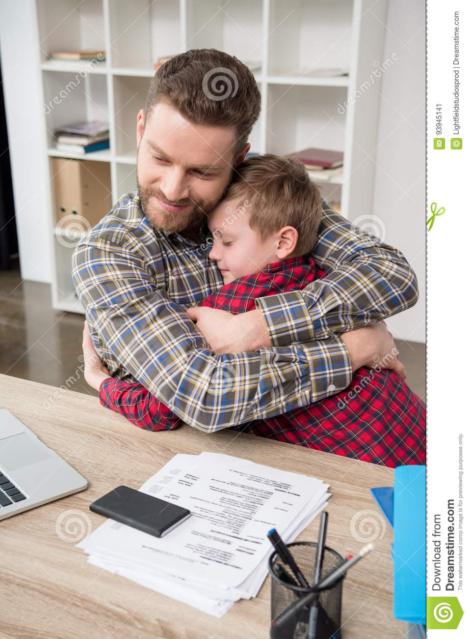 Father businessman hugs his son