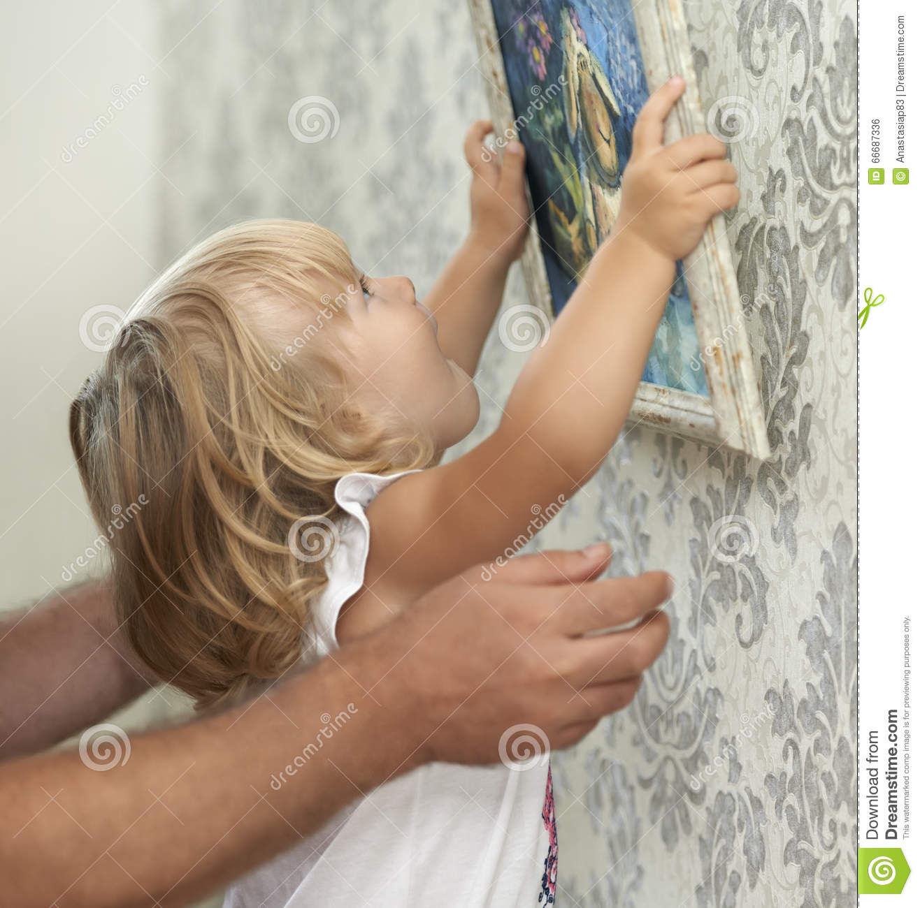 Father and child hanging picture on the empty wall
